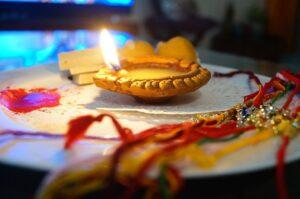 Plateau avec un rakhi (bracelet) et un deepak, petite lampe allumé