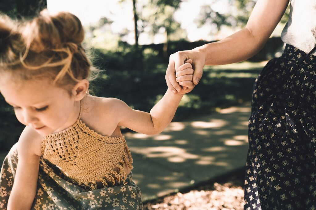 petite fille tenant la main de sa mère