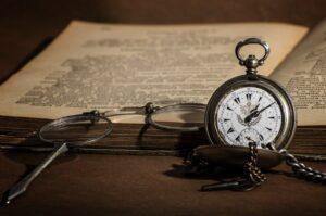 Livre, lunettes et ancienne montre déposés sur une table