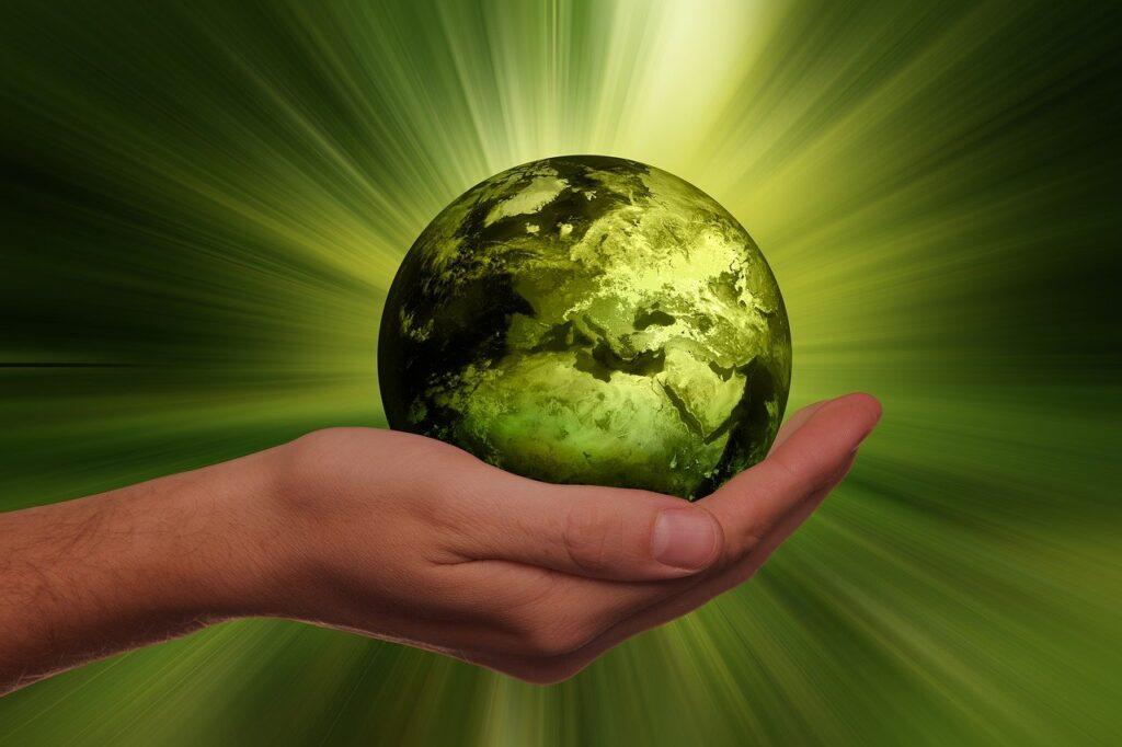 la terre dans une main et des rayons de lumière verte
